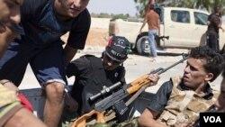 Pemberontak Libya menaiki sebuah truk pick up untuk menuju garis depan di Zawiya, Libya barat (13/8).