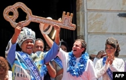 Rio de Janeiro's Mayor Eduardo Paes (2nd R) hands over the city's ceremonial key to the Rei Momo, or Carnival King Wilson Neto (L) at Cidade Palace, Feb. 13, 2015.