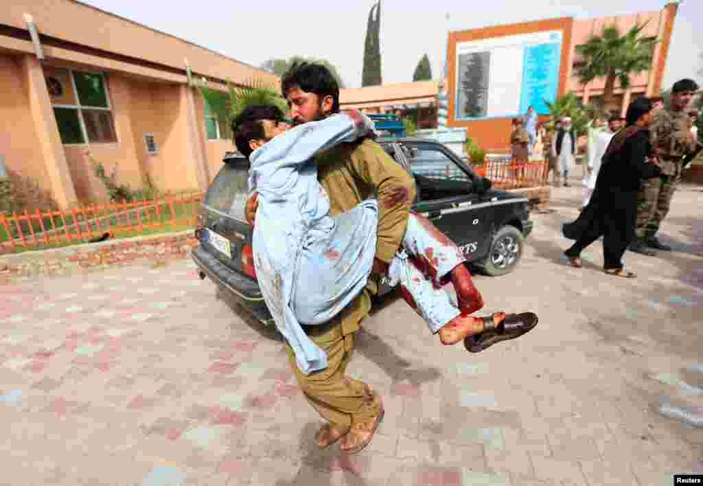 An injured man is carried to a hospital after a car bomb in Jalalabad city, Afghanistan.