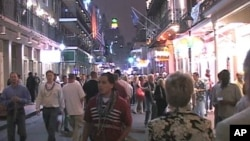 FILE - Tourists and locals walk down Bourbon Street in New Orleans