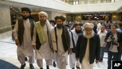 FILE - In this May 28, 2019 file photo, Mullah Abdul Ghani Baradar, the Taliban group's top political leader, third from left, arrives with other members of the Taliban delegation for talks in Moscow, Russia. U.S. envoy Zalmay Khalilzad and the Taliban ha
