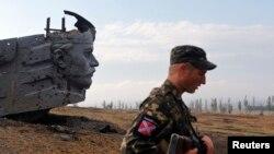 Un separatista prorruso vigila cerca de un monumento cerca de la ciudad de Donetsk.