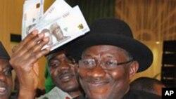 Presiden Nigeria, Goodluck Jonathan mengambil uang naira dari sebuah ATM di Abuja (foto: dok). Bank sentral mendevaluasi mata uang naira.