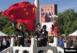 中国武警士兵在拉萨举行的西藏自治区成立50周年庆祝活动升旗仪式期间展开中国国旗。(2015年9月8日)