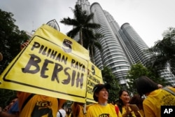 "Activists from the Coalition for Clean and Fair Elections (BERSIH) show a placard reading ""Clean Election BERSIH"" in front of the Petronas Towers during a rally in Kuala Lumpur, Malaysia Saturday, Nov. 19, 2016."