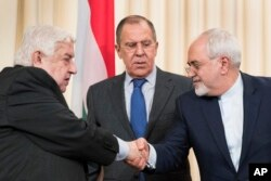 Russian Foreign Minister Sergei Lavrov, center, stands in the middle as Syrian Foreign Minister Walid Muallem, left, and Iranian Foreign Minister Mohammad Javad Zarif shake hands after a shared press conference following their talks focused on Syria in Moscow, Russia, April 14, 2017.