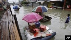 菲律宾首都附近居民在洪水淹没的道路上使用临时拼凑的筏子及临时搭建的桥梁逃离洪灾