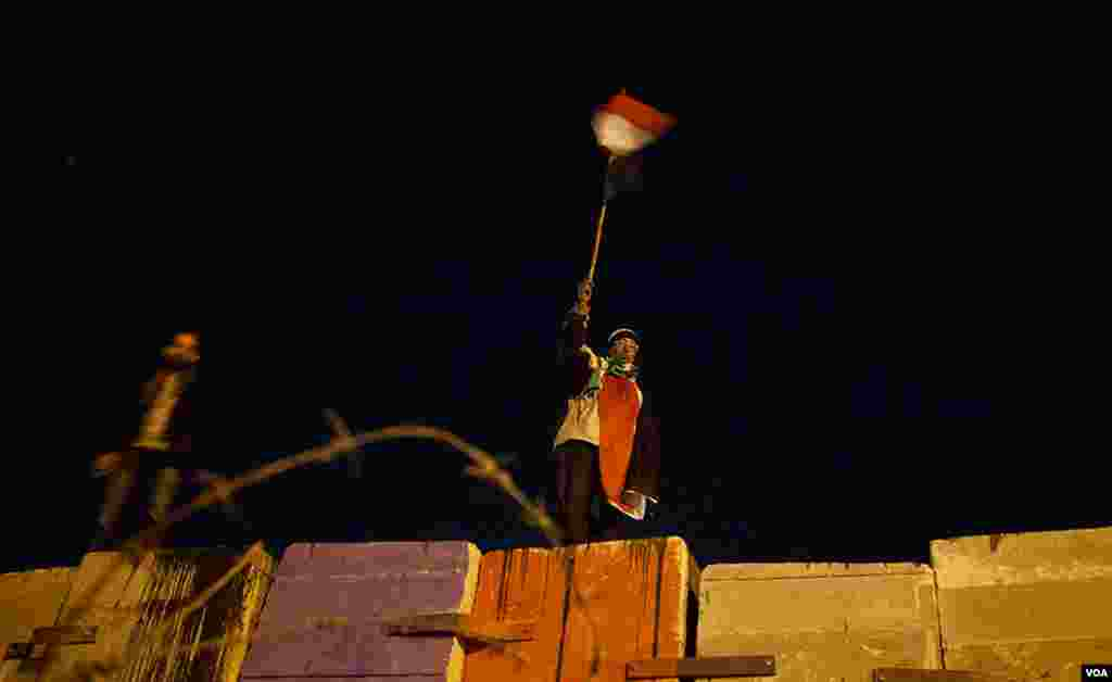 An anti-Morsi protester waves an Egyptian flag atop a huge wall erected by Egypt's Republican Guard to prevent demonstrators from amassing around the Presidential Palace. (Yuli Weeks for VOA)