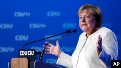German Chancellor Angela Merkel gestures during her speech at a state election campaign in Munich, Germany, Sept. 24, 2021, two days before Sunday's general election.