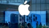 FILE - People check out the latest iPhone 13 handsets at an Apple Store in Beijing, China, Sept. 28, 2021. Amazon's audiobook service Audible and phone apps for reading the Quran and Bible have become inaccessible for users in mainland China.