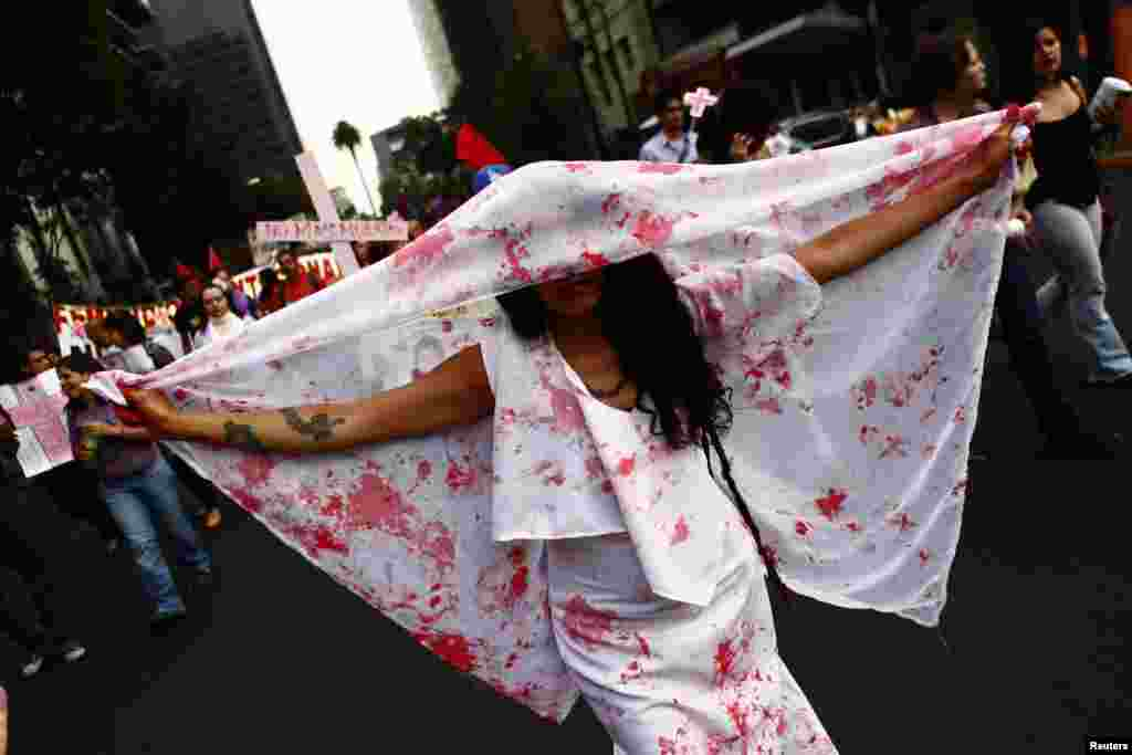 A woman holds a sheet with stains to represent blood during a demonstration to demand justice for women, who are the victims of violence, in Mexico City, Mexico, Mar. 8, 2013.
