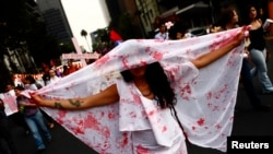 FILE - A woman holds a sheet with stains to represent blood during a demonstration to demand justice for women, who are the victims of violence, in Mexico City, Mexico.