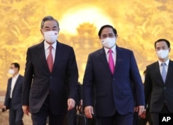 Vietnamese Prime Minister Pham Minh Chinh (R) and Chinese Foreign Minister Wang Yi (L) walk into meeting room in Hanoi, Vietnam, Sep.11, 2021.