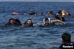 Di dân và người tị nạn Syria và Iraq bơi về phía bờ khi chiếc thuyền của họ bị xì hơi cách đảo Lesbos của Hy Lạp 100 mét, ngày 13 tháng 9, 2015.