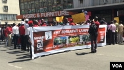 """""""President Robert Mugabe must go!"""" protesters shout in Harare. The opposition accuses the 92-year-old leader of ruining the once-vibrant economy of Zimbabwe and disregarding human rights. (C. Mavhunga/ VOA)"""