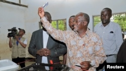 FILE - John Magufuli displays his ballot paper before casting his vote in the presidential and parliamentary election at his hometown Chato district, in Geita region, Tanzania, Oct. 25, 2015.
