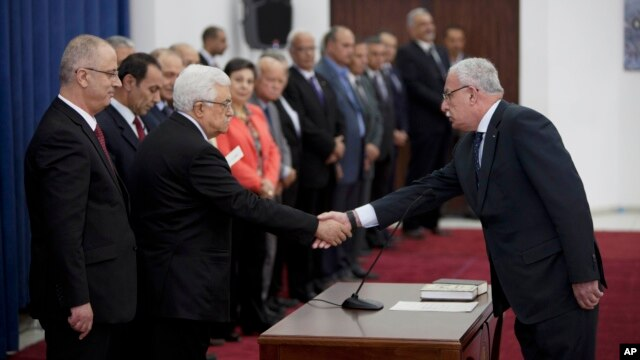 Palestinian Foreign Minister Riyad al-Malik, right, shakes hands with President Mahmoud Abbas during a swearing-in ceremony of its unity government in the West Bank city of Ramallah, June 2, 2014.