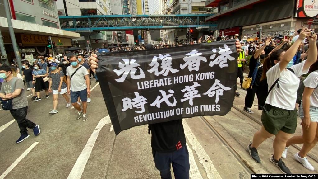 7月1日港版国安法实施第一日,数以万计香港人聚集在铜锣湾上街游行,有人高举被当局批评有港独含意的反送中运动旗帜(美国之音/汤惠芸)