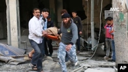 This photo provided by the anti-government activist group Aleppo Media Center (AMC), an anti-Bashar Assad activist group, which has been authenticated based on its contents and other AP reporting, shows Syrian men carrying a covered dead body after a government airstrike attack in the al-Mayssar neighborhood, in Aleppo, April 3, 2014.