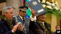 Bolivia's President Evo Morales, wearing garland made from coca leaves, holds up the folder containing the newly-signed coca law at the presidential palace in La Paz, Bolivia, March 8, 2017.