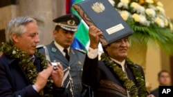 Bolivia's President Evo Morales holds up the folder containing the newly-signed coca law at the presidential palace in La Paz, Bolivia, Wednesday, March 8, 2017. (AP Photo/Juan Karita)