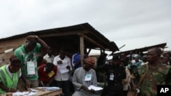 Soldiers and police stand guard as electoral officials count ballot papers after the National Assembly election in Ibadan, Nigeria,Saturday, April 9, 2011.
