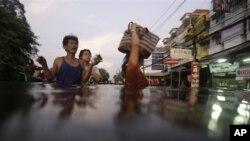 침수된 길을 따라 이동하고 있는 방콕 시민들