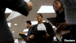 FILE - Job seekers listen to prospective employers during a job hiring event for marketing, sales and retail positions in San Francisco, California, June 4, 2015.