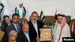 시리아 반군 연합의 모아즈 알카티브 대표(가운데)가 27일 카타르 도하에서 새 시리아 대사관 현판을 칼리드 빈 모하메드 알아티야 카타르 외무장관에게 전달하고 있다. 카타르를 포함한 아랍연맹은 시리아 반군 연합을 시리아의 유일한 대표로 인정했다.