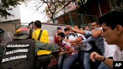 Los funcionarios venezolanos de la guardia nacional bolivariana se enfrentan a estudiantes universitarios durante una protesta fuera del Tribunal Supremo en Caracas, Venezuela, el viernes 31 de marzo de 2017.