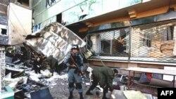 Cảnh sát Afghanistan canh gác trong lúc nhân viên bảo vệ xem xét thiệt hại sau vụ đánh bom tự sát ở Kabul, ngày 14/2/2011