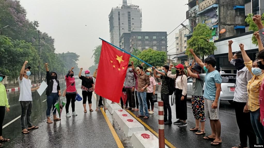 资料照片:在缅甸仰光举行的反对中国的示威活动中,反政变抗议者举着一面中国国旗,准备将其焚烧。(2021年4月5日)
