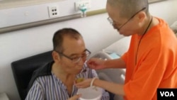 FILE - Chinese dissident and Nobel Prize laureate Liu Xiaobo, left, is attended to by his wife Liu Xia in a hospital in China.