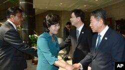 Ketua delegasi Korea Utara Kim Song Hye (tengah) berjabat tangan dengan delegasi Korea Selatan Kwon Young-yang (kanan), setibanya di Panmunjom, Paju, utara kota Seoul, Korea Selatan (9/6).