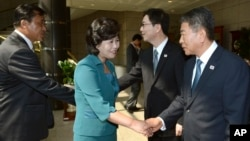 The head of North Korea's delegation Kim Song Hye, center, shakes hands with South Korean delegate Kwon Young-yang, right, upon their arrival for a meeting at the southern side of Panmunjom, in Paju, north of Seoul, South Korea, June 9, 2013. (Photo released by S. Korean Unification Ministry)