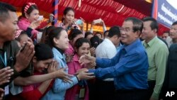 FILE PHOTO - Prime Minister Hun Sen greets garment workers during a visit to a factory outside of Phnom Penh, Cambodia, Wednesday, Aug. 30, 2017.