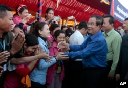FILE - Prime Minister Hun Sen greets garment workers during a visit to a factory outside of Phnom Penh, Cambodia, Wednesday, Aug. 30, 2017.