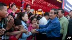Prime Minister Hun Sen greets garment workers during a visit to a factory outside of Phnom Penh, Cambodia, Wednesday, Aug. 30, 2017. Hun Sen embarked on a country-wide trip to visit the nation's factory workers to hear their hopes and concerns in person.