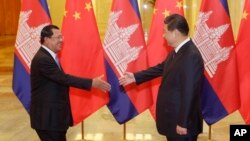 Cambodian Prime Minister Hun Sen (L) shakes hands with China's President Xi Jinping before a meeting at the Great Hall of the People in Beijing, Nov. 7, 2014.