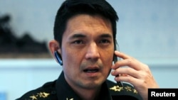 FILE - Winthai Suvaree, a spokesman for the Thai military government's NCPO, speaks on his mobile phone during an interview with Reuters at the Royal Army headquarters in Bangkok, Sept. 11, 2014.