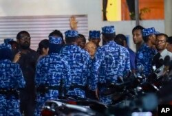 Police arrest Maumoon Abdul Gayoom, center, a former Maldives president and opposition leader, after the government declared a 15-day state of emergency in Male, Maldives, Feb. 6, 2018.