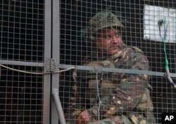 FILE - An Indian army soldier looks from inside an army vehicle at the Indian air force base in Pathankot, Jan. 4, 2016, on the third day of an attack by militants.