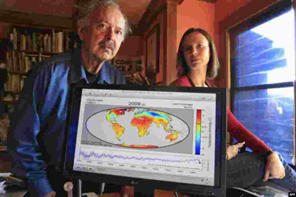 In this Friday, Oct. 28, 2011 photo, Richard Muller, left, and his daughter, Elizabeth Muller, right, pose with a map from their study on climate at their home in Berkeley, Calif. A new study of Earth�s temperatures going back more than 200 years finds th