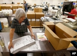 Workers at the Maricopa County recorder's office go through ballots Nov. 8, 2018, in Phoenix. There are several races too close to call in Arizona, especially the Senate race between Democratic candidate Kyrsten Sinema and Republican candidate Martha McSally.
