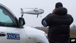FILE - A member of the Organization for Security and Cooperation in Europe (OSCE) mission to Ukraine watches one of the watchdog's drone take off near the city of Mariupol, eastern Ukraine, Oct. 23, 2014.