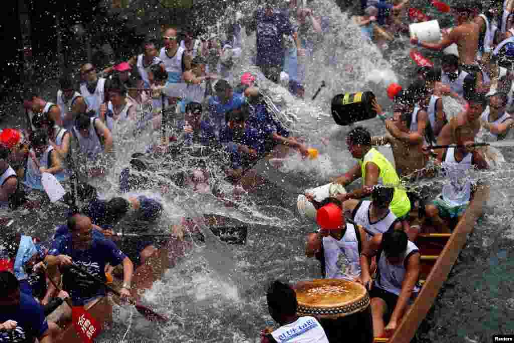 Những người tham gia té nước vào nhau trong một buổi lễ mừng Tết Đoan Ngọ tại cảng cá Aberdeen, Hong Kong.