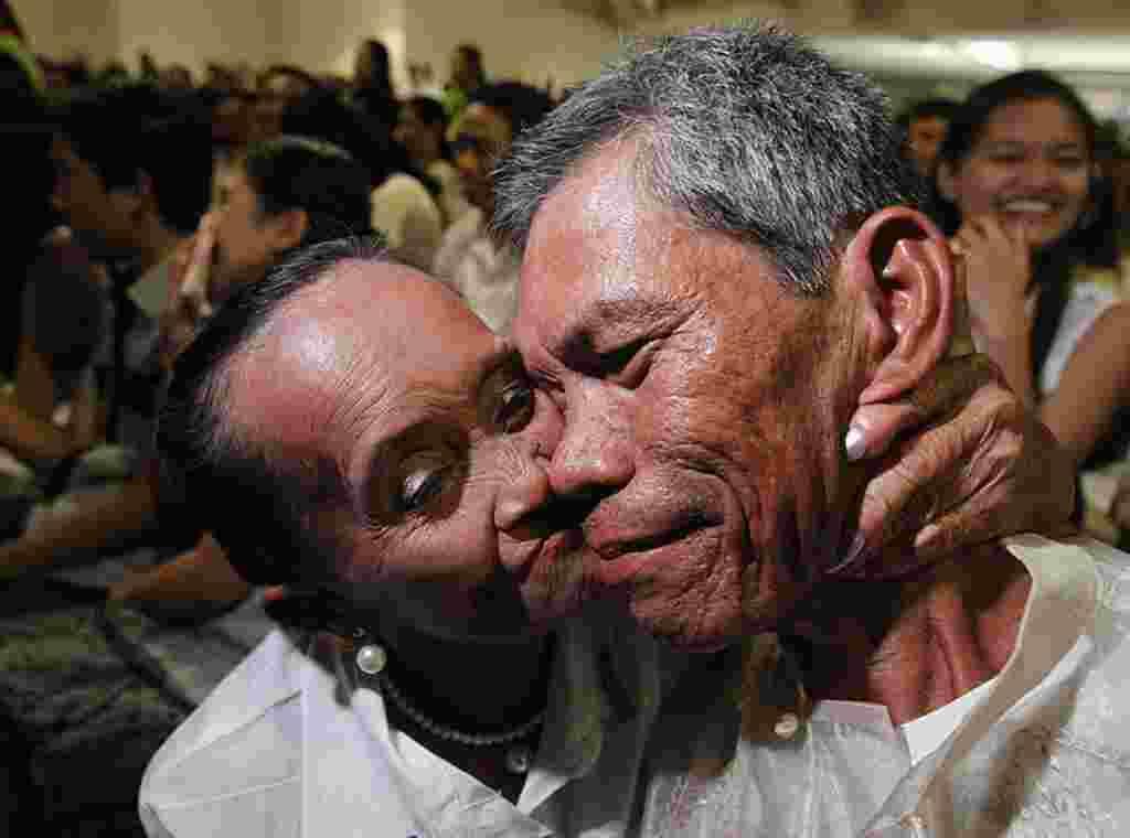 Seorang pengantin perempuan berusia 66 tahun mencium pipi suami barunya yang berusia 54 tahun dalam sebuah upacara pernikahan massal dalam rangka hari Valentine di Paranaque, Metro Manila, 14 Februari (REUTERS).