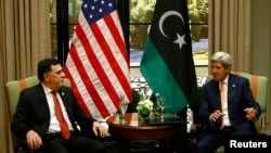 PM pemerintahan baru Libya Faye al-Sarraj (kiri) dan Menlu AS John Kerry dalam pertemuan bilateral di Wina, Austria (16/6).
