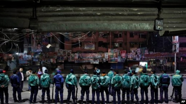 Bangladeshi policemen stand guard outside offices of the main opposition Bangladesh Nationalist Party during nationwide 48-hour strike on eve of general elections, Dhaka, Bangladesh, Jan. 4, 2014.