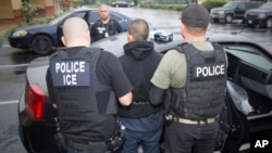 FILE - This photo released by U.S. Immigration and Customs Enforcement shows foreign nationals being arrested, Feb. 7, 2017, during a targeted enforcement operation conducted by U.S. Immigration and Customs Enforcement (ICE).